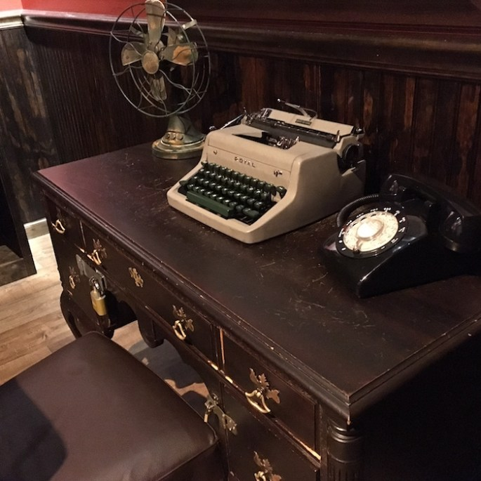An old desk with drawers locked shut. Atop the desk are an old fan, typewriter, and rotary phone.