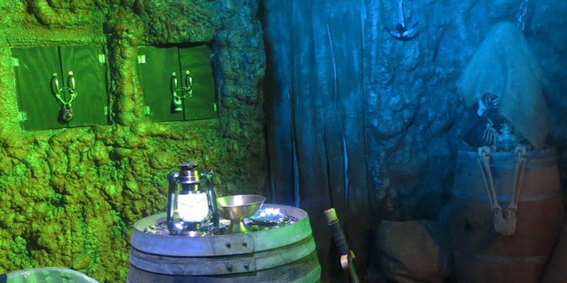 In-game. The pirate's grotto lit green and blue. Booty lays atop a barrel. Locked cabinets are in the background as is a skelaton covered in burlap.