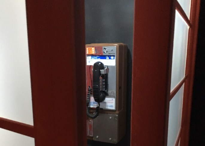Interior of the phone booth: A pay phone is mounted to the wall.