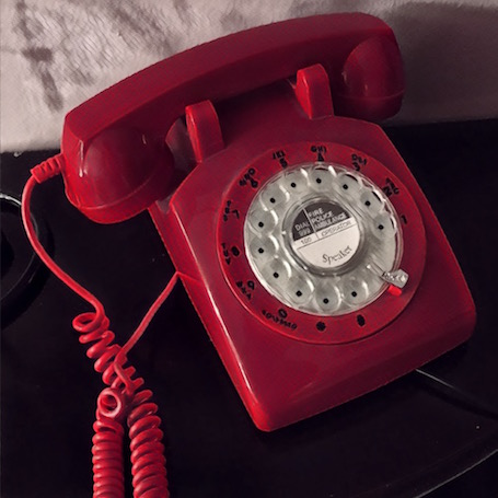 Stylized black, white, and red photo of a rotary phone.