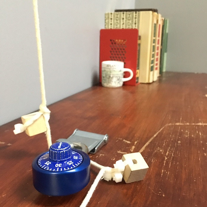 A padlock securing a string atop a beatup desk. A few books and a mug rest in the background.