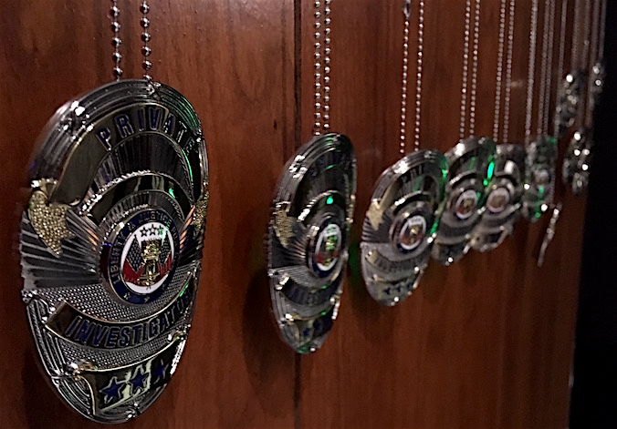 "A line of a dozen ""Private Investigator"" badges hanging on chains along a wood paneled wall."