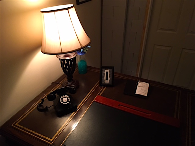 In game: A large wood desk with a light, and rotary phone.