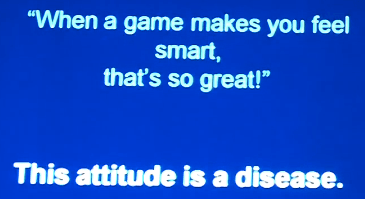 "Screenshot of video, blue background with white writing reads, ""'When a game makes you feel smart, that's so great!' This attitude is a disease."""