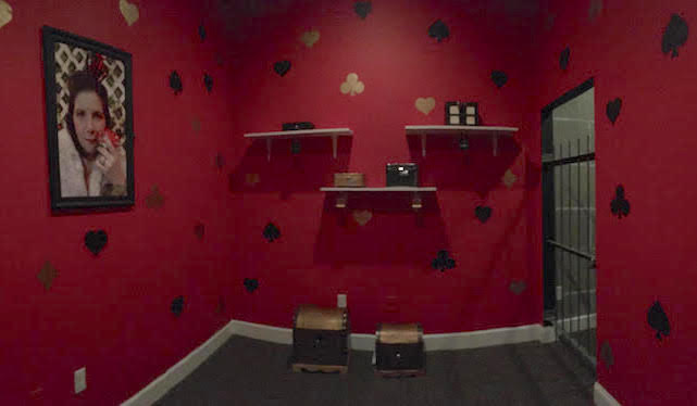 In game - the Queen of Heart's dungeon. The walls are painted red with card suites on it, and many locked boxes sit on shelves.