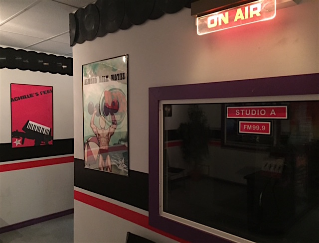 """In-game: A studio with an """"On Air"""" sign illuminated. Band art hangs on the walls."""