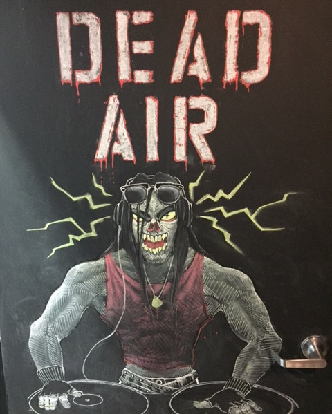 "In-game: Door art of a zombie at a turntable. It reads ""DEAD AIR"""