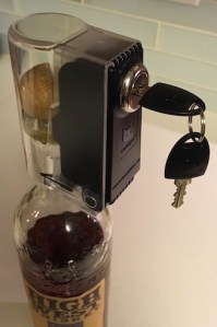 Tantalus Wine and Liquor Bottle Lock secured over a wide mouthed bottle of whiskey.