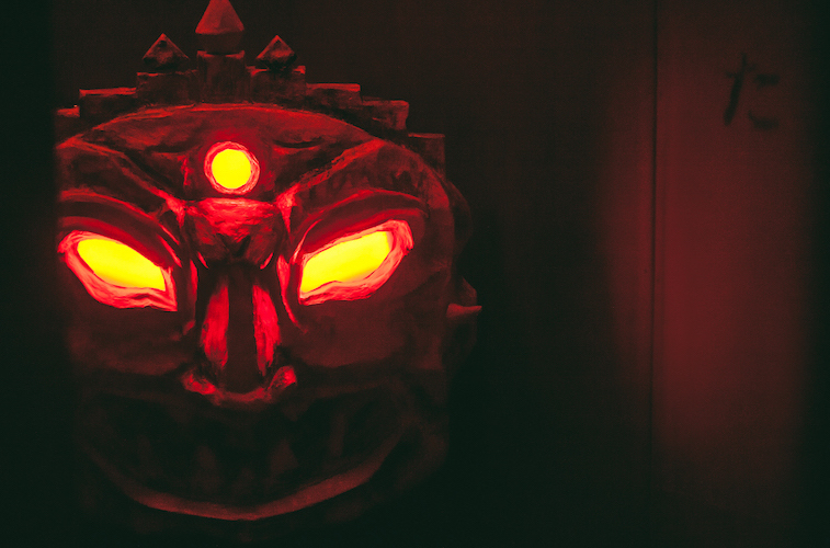 In-game: A red glowing demon's face in the shadows.