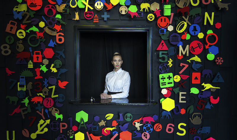 In-game: an actress sitting in a window surrounded by a variety of brightly colored symbols.