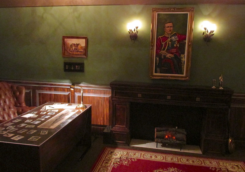 In-game: an office with a large red chair at the desk. A fireplace, and a portrait of a young soldier hanging over it.