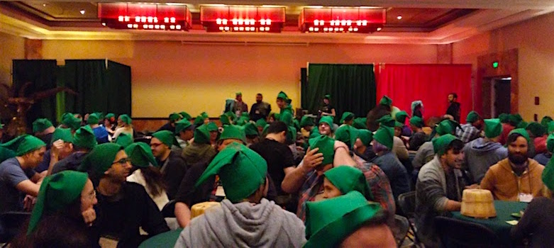 In-game: A ballroom full of seated players all wearing green Link elf hats.