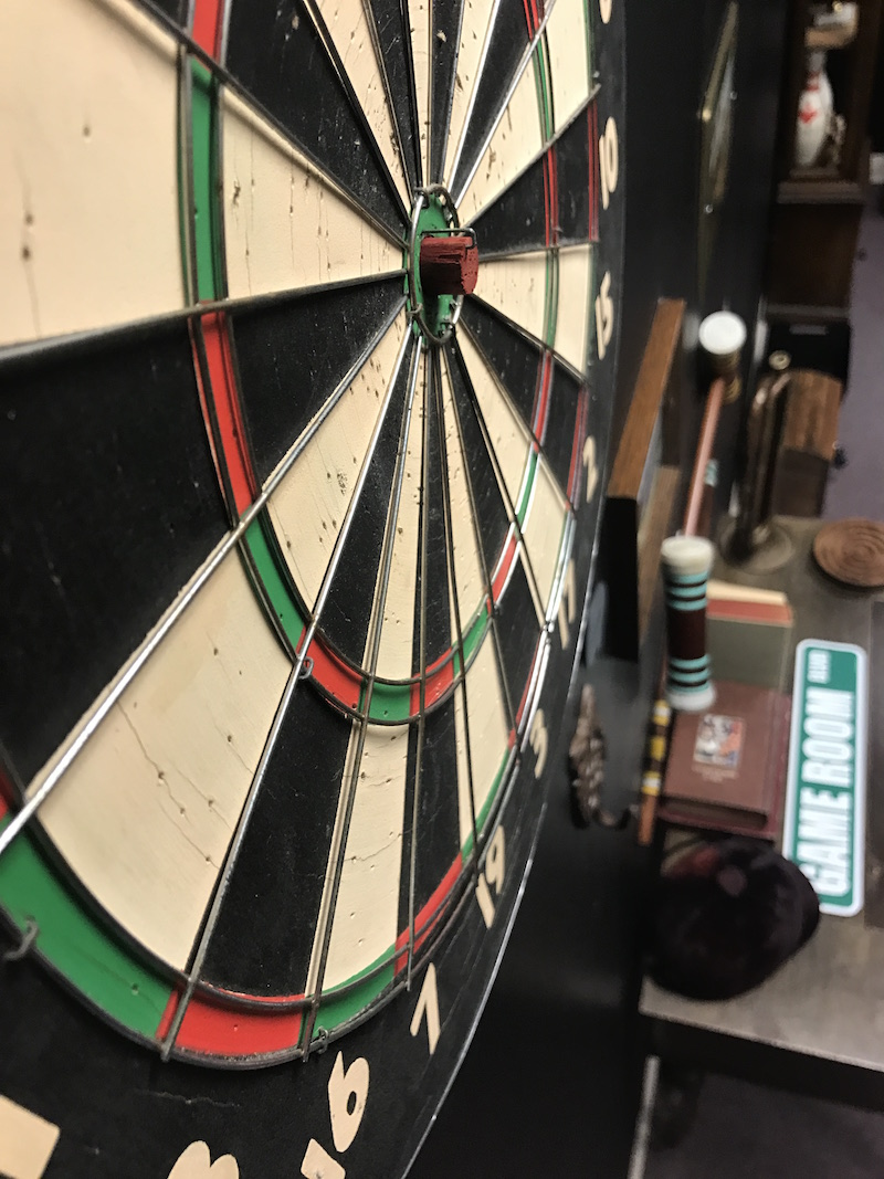 In-game: An artistic shot of a dartboard on the wall, assorted other props are on a table below.