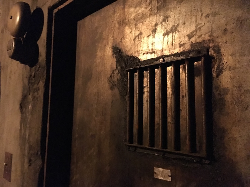 In-game: A weathered metal prison door with an alarm bell mounted to the concrete wall beside it.