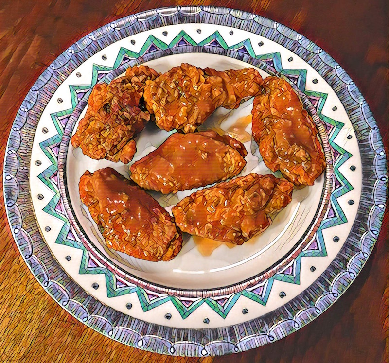 Mosaic photo of 6 buffalo wings sitting atop an ornately decorated plate upon a wood table.
