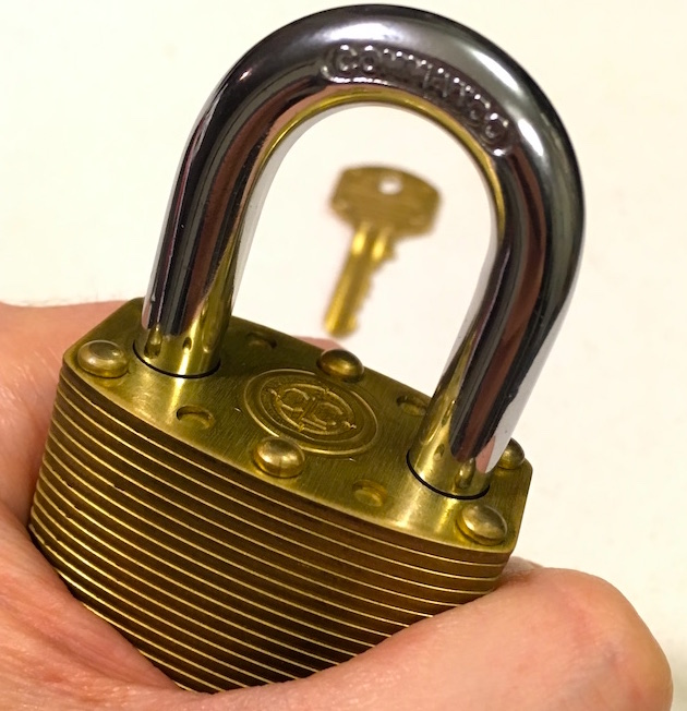 Commando Lock Marine Brass closeup of the lock, visible through the shackle is the key blurred in the backround.