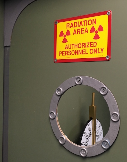 In-game: A submarine door with a radiation warning. Through the porthole is a depth controller.