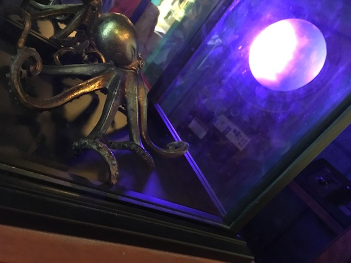 In-game: A glass display with an bronze octopus inside. Beyond the glass, a porthole is illuminated blue.