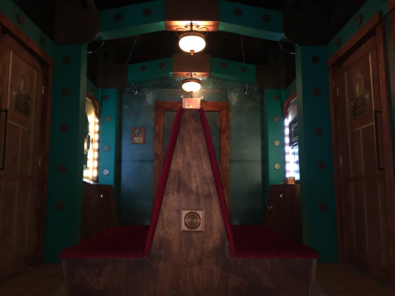 In game: The ornate interior of the vessel has a large bench in the middle and large copper doors with green walls covered in large rivets.