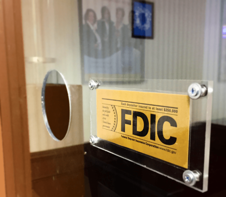 In-game: a closeup of a bank teller's window with the FDIC insurance sticker in the foreground.