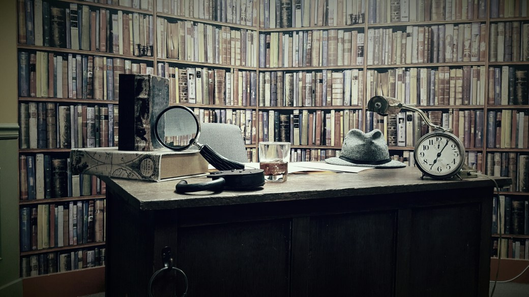 A staged image on the set of a desk in front of many books. Props are staged on the desk.