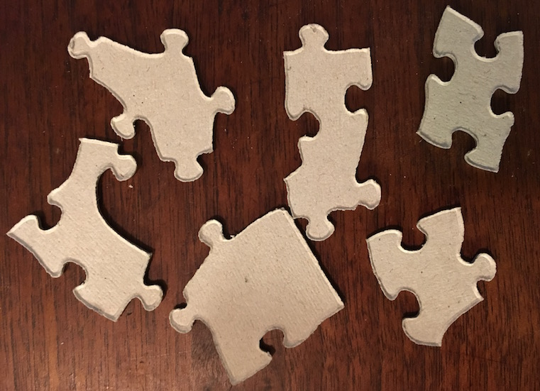 An assortment of 6 puzzle pieces flipped over so that the viewer focuses on their irregular shape.