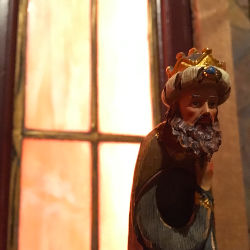 In-game: A closeup of a wooden statue of a king backlit by beautiful orange stained glass windows.