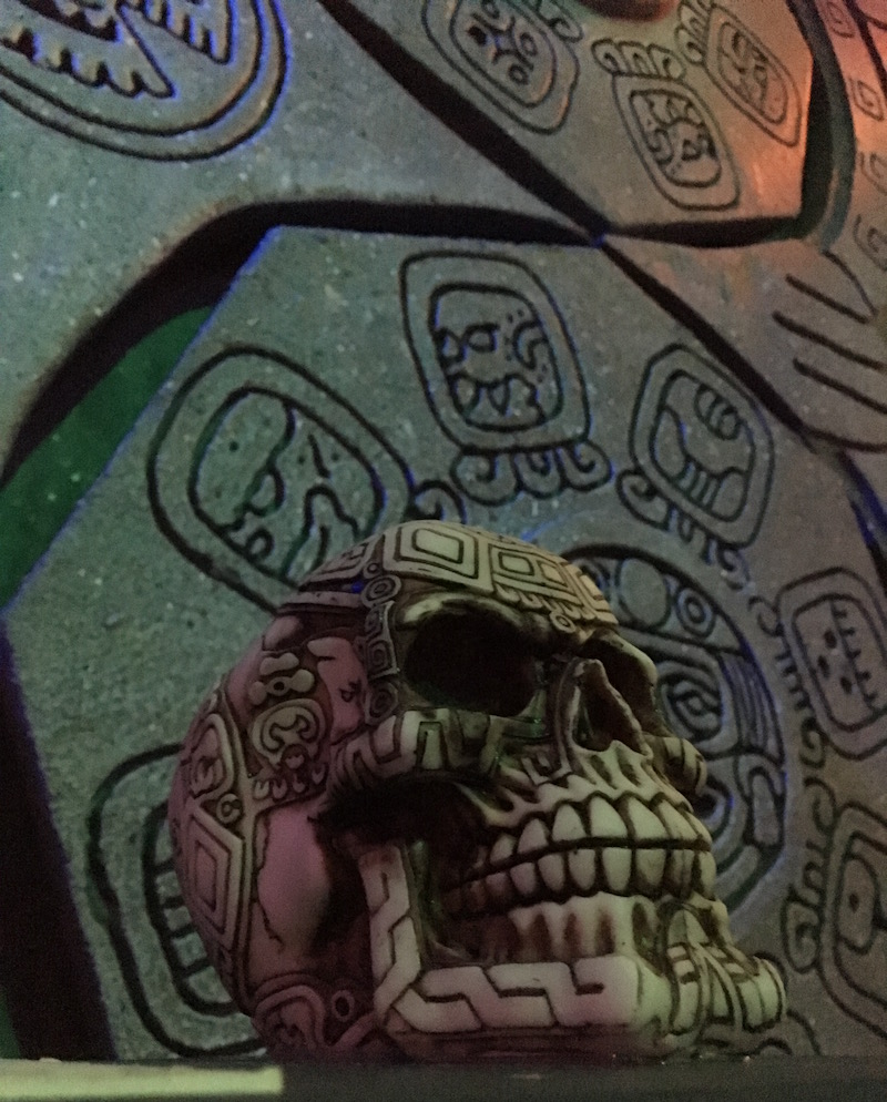 In-game: An engraved human skull rests in front of a stone wall with symbols carved into it