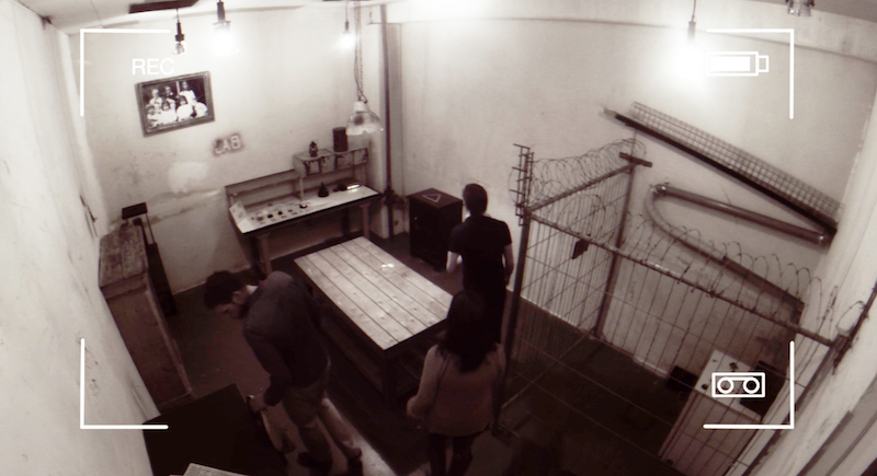 In-game: Image from the security camera of a menacing lab with a work table, and a cage surrounded by barbed wire.