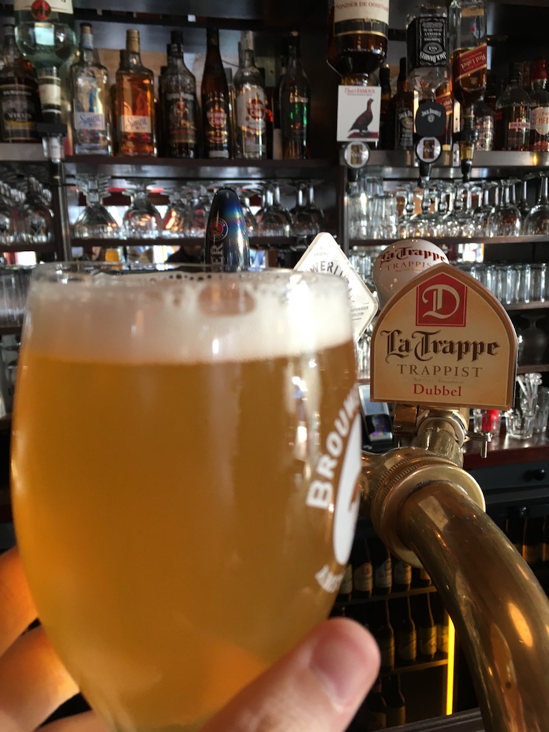 "A beer held up in front of a tap that reads, ""La Trappe: Trappist"""