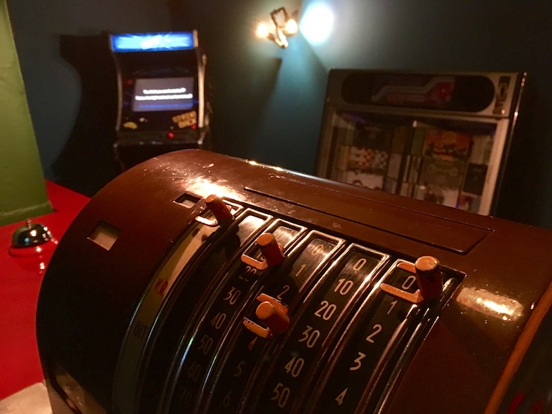 In-game: Close up of an old cash register with an arcade cabinet and a jukebox in the background.