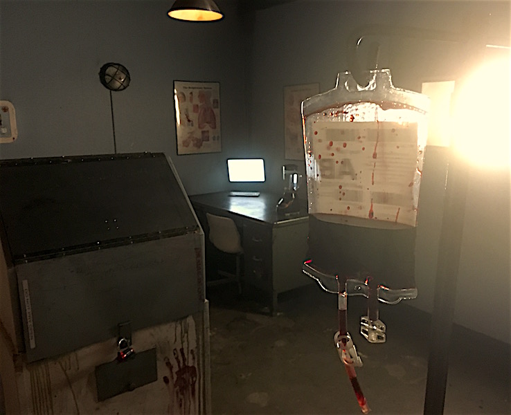 In-game: A dark and bloody medical lab with a bag of AB blood hanging in the foreground.