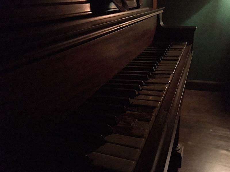 In-game: Closeup of heavily damaged piano keys in a dim room.