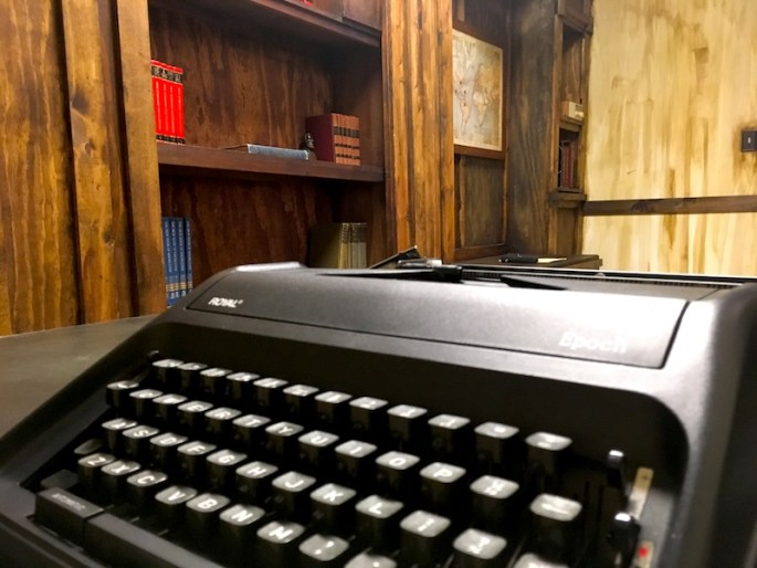 In-game: A typewriter on a desk in the foreground. A large wooden bookcase in the background.