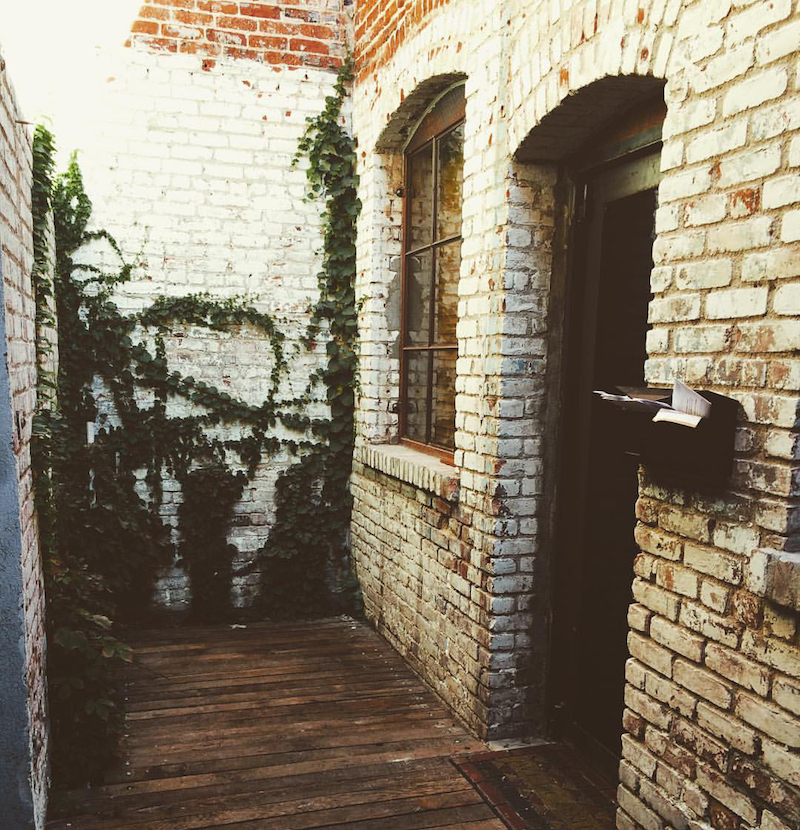 Game exterior: The old white bricked entrance to Occam's apartment.