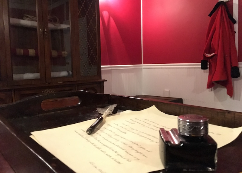 In-game: Closeup of a handwritten letter with a quill pen and ink. A red British officer's jacket hangs on the wall in the distance.