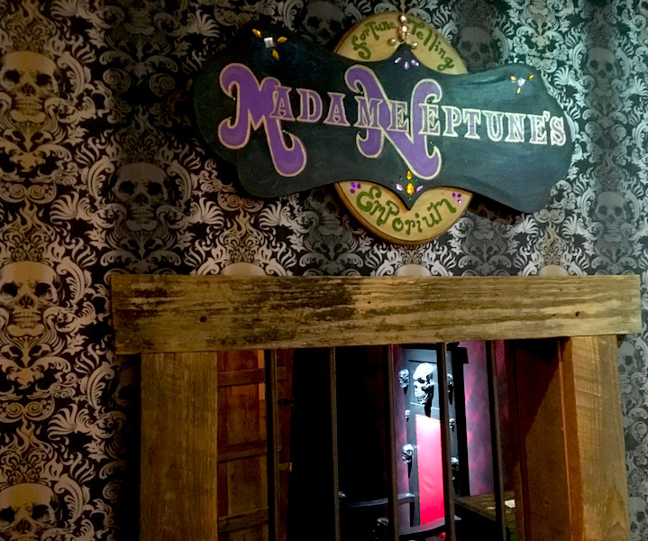 In-game: The sign for Madame Neptune's Fortune Telling Emporium. Through a window below it a throne of skulls sits in the background.