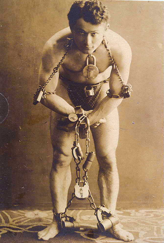 Harry Houdini bound by his wrists, ankles forearms, and neck in chains and many locks.