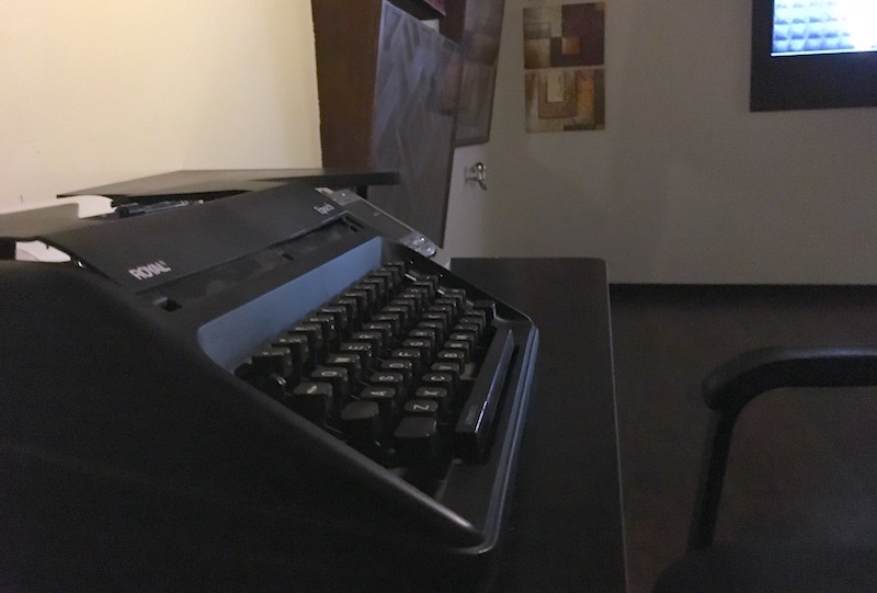 In-game: A typewriter on a desk in a dark room. A large maze hangs on the wall in the distance.