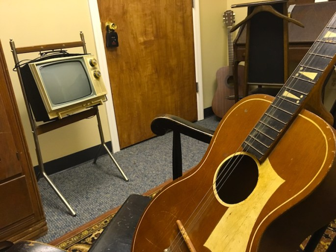 In-game: A guitar in the foreground in a crappy old apartment. Another guitar rests in the background.
