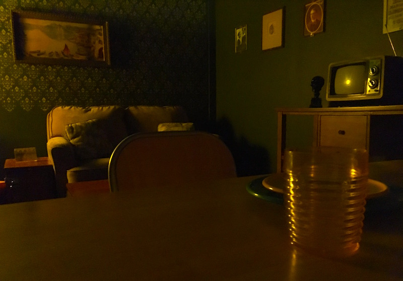In-game: A creepy apartment living space with green walls. A sofa, and television sit in the background. A set kitchen table in the foreground.