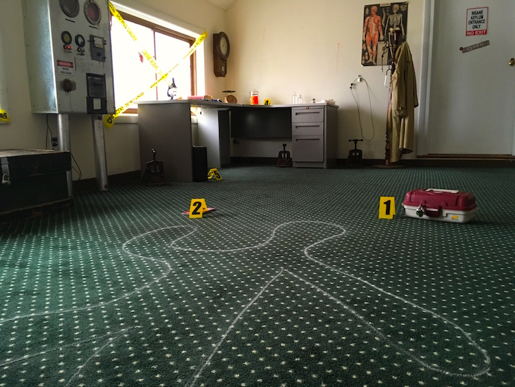 In-game: A chalk outline of a body in the middle of a lab-esque crime scene.