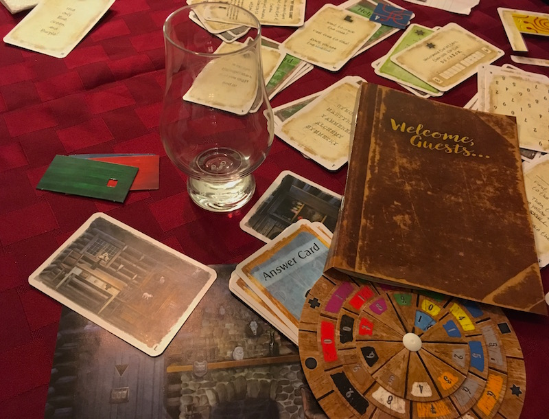 "In-game: A mess of cards, the decoder wheel, images of the cabin's rooms, and a book that reads, ""Welcome Guests..."""