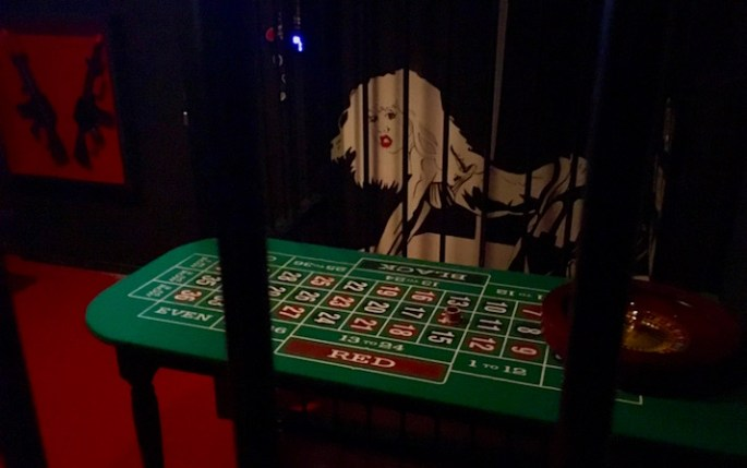 In-game: A casino setting with cages. A roulette table in the foreground, guns and a painting of a stripper resembling Nancy in the background.