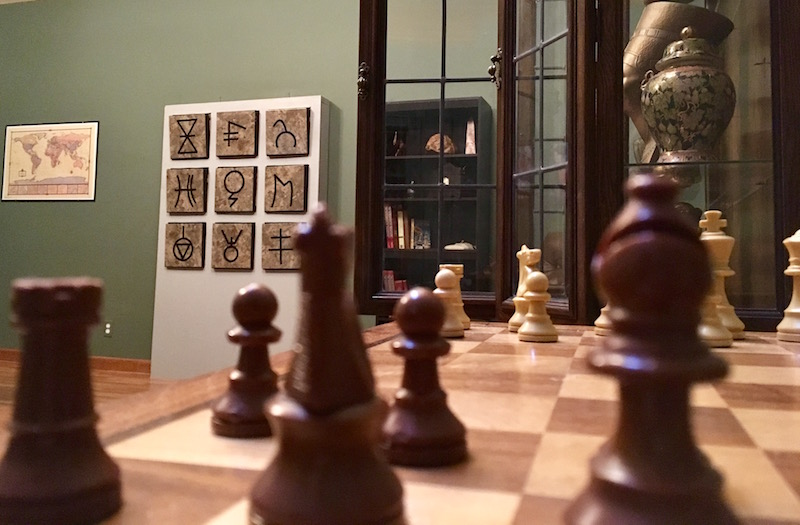 In-game: A broad shot of the room, a wall of ruins in the background along with a cabinet of artifacts. A chess board is staged blurred in the foreground.