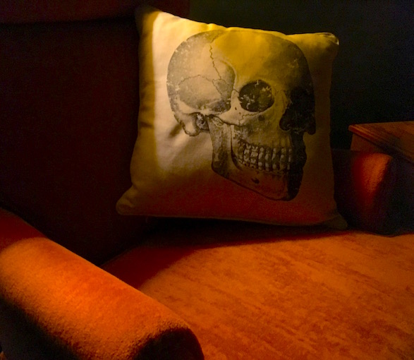 A white skull pillow sitting on a big comfortable orange chair in a dark room.