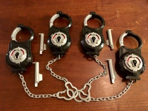 4 Break Free handcuffs chained together with their picks beside them.