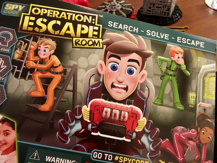 Spy Code Operation: Escape Room box features cartoon kids solving puzzles, and one kid in a chair sweating with the