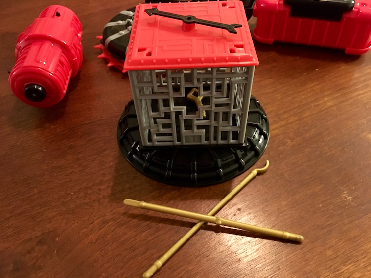 A grated cage with a spinner arrow on top, a key inside, and a pair of sticks beside it.