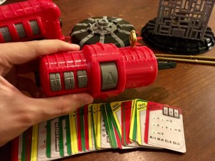 Quiz Master: A red tube with input for a 3 digit number and a letter answer. A key is protruding from its side. An array of corresponding puzzle cards are fanned in front of it.